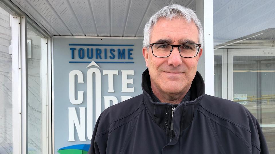 Un homme aux cheveux blancs qui porte des lunettes sourit devant les locaux de Tourisme Côte-Nord.