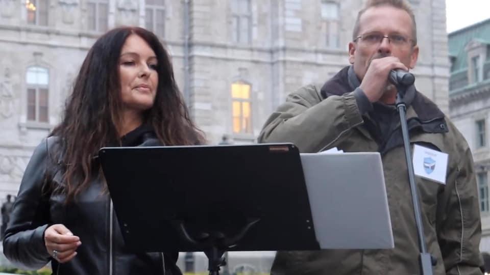 Une femme et un homme derrière un lutrin, devant l'Assemblée nationale du Québec. L'homme parle dans un microphone.