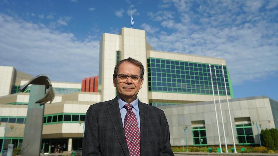 Un homme en complet se dresse devant un édifice gouvernemental