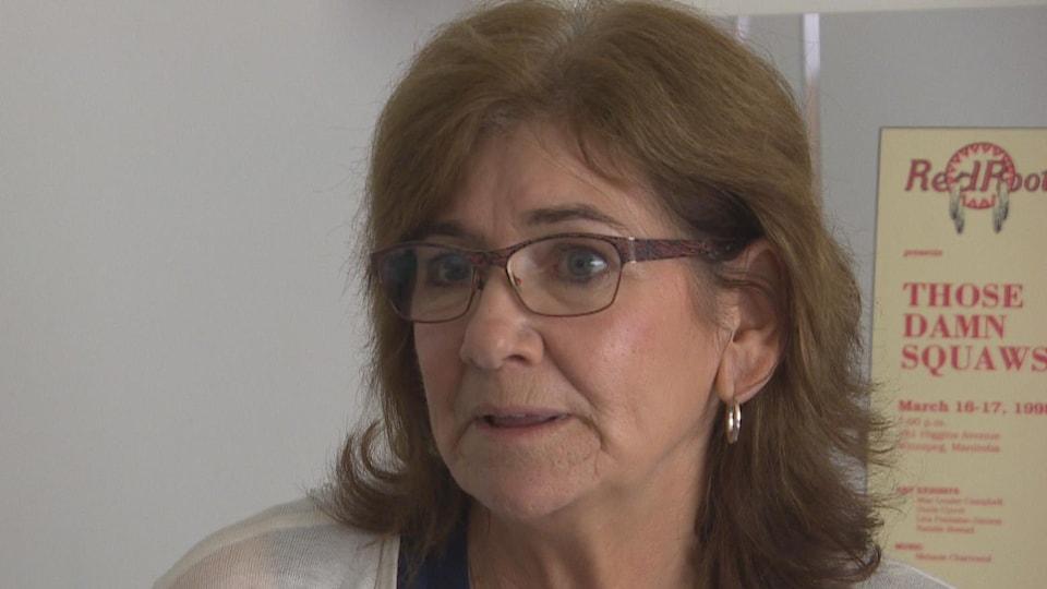 Une dame avec des lunettes s'exprime, l'air concerné.
