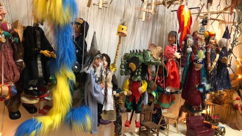 Des marionnettes accrochées sur un mur.
