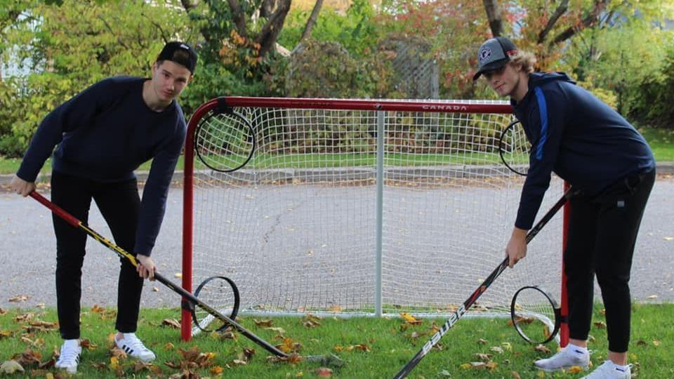 Les deux joueurs posent avec leur bâton au bord de la rue devant un filet de hockey de rue.