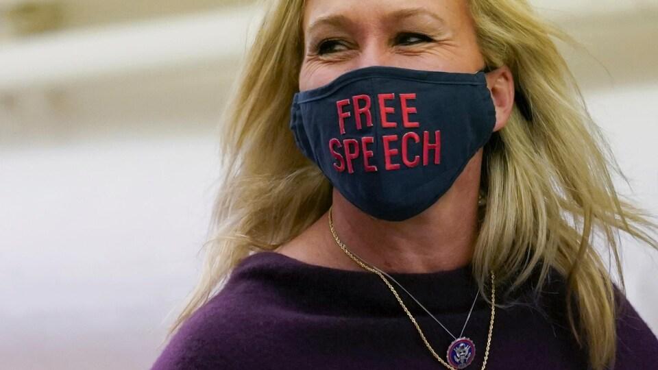 Marjorie Taylor Greene, qu'on voit sourire en raison de son regard, porte un masque disant « liberté d'expression ».
