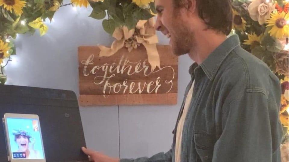 Un homme regarde un iPad et sourit.