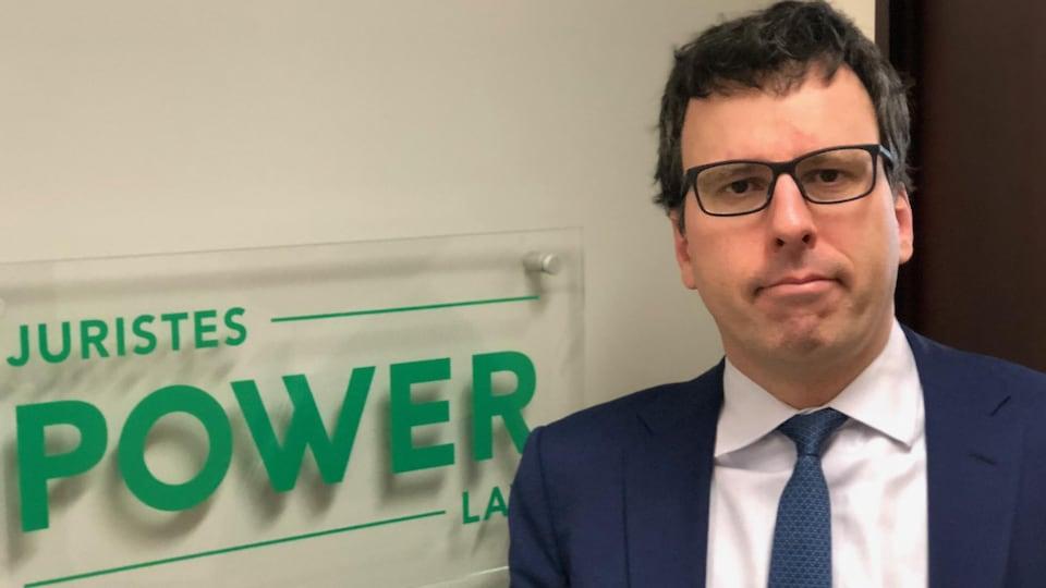 Mark Power devant l'affiche de son bureau Juristes Power.