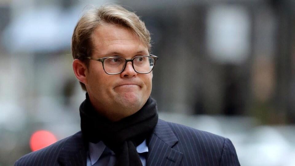 Un homme en habit avec des lunettes et un foulard.