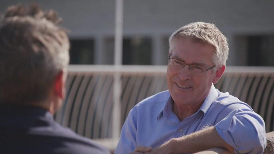 Un homme discute avec un autre homme