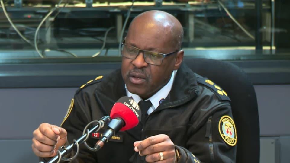 Photo d'un homme portant un uniforme de policier derrière un micro dans un studio de radio