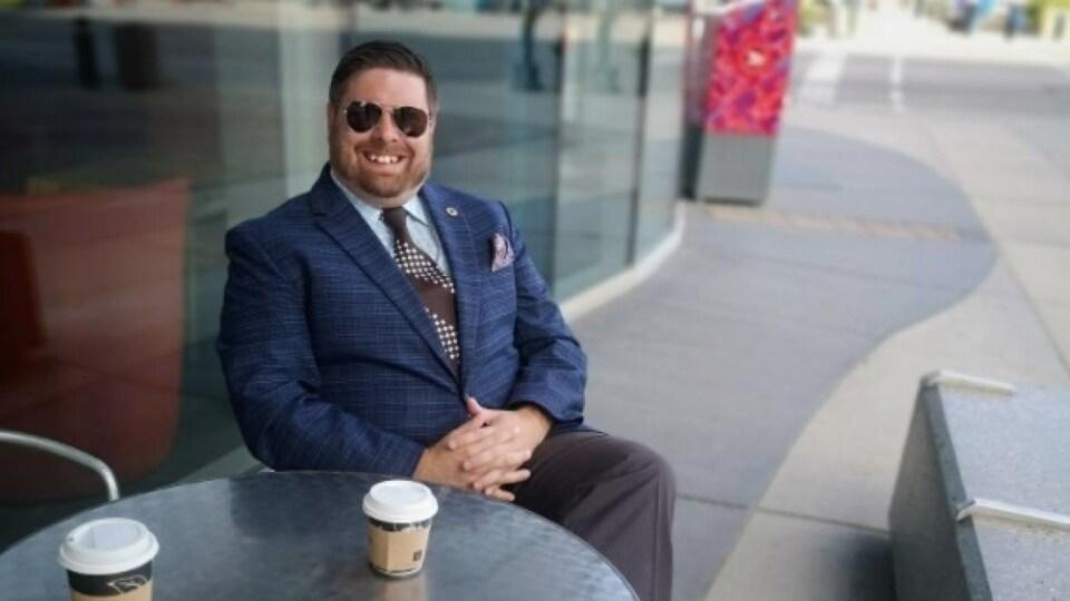 Mark Zielke devant une table d'un café.