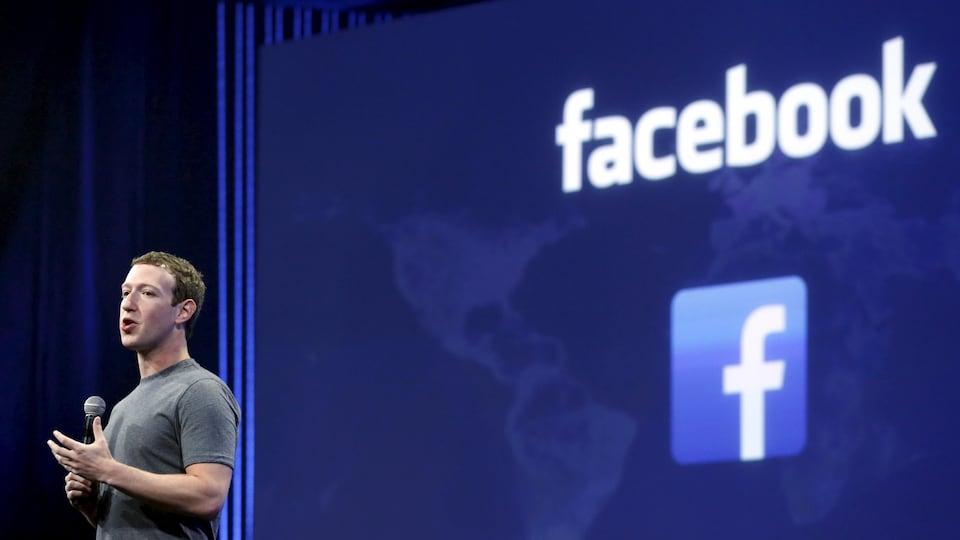 Le fondateur de Facebook, Mark Zuckerberg, donne une conférence devant un grand écran où projeté le logo de Facebook.