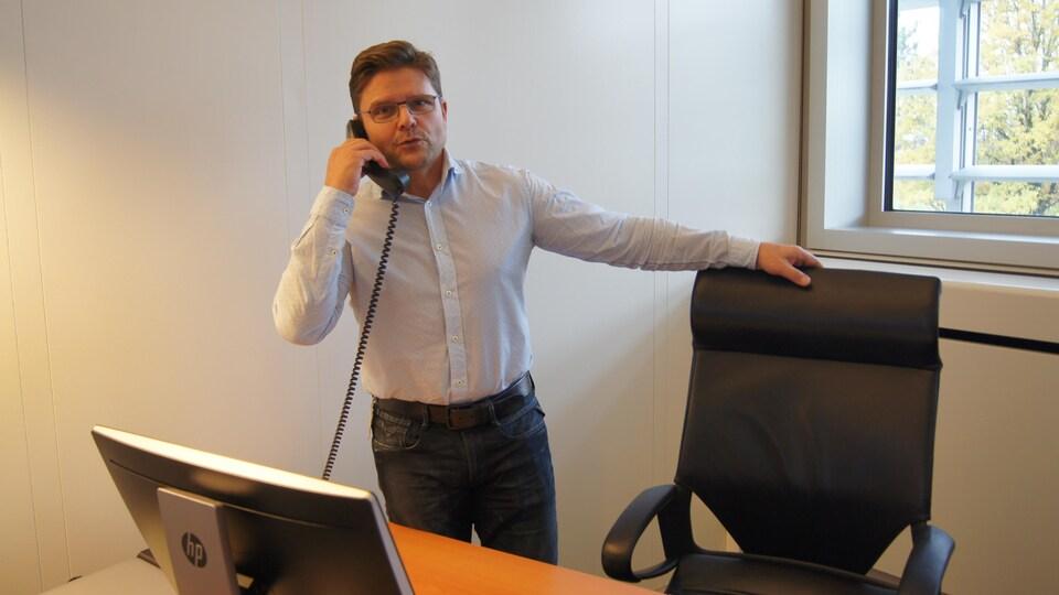 On voit M. Mosimann, debout, derrière son bureau, en train de parler au téléphone.