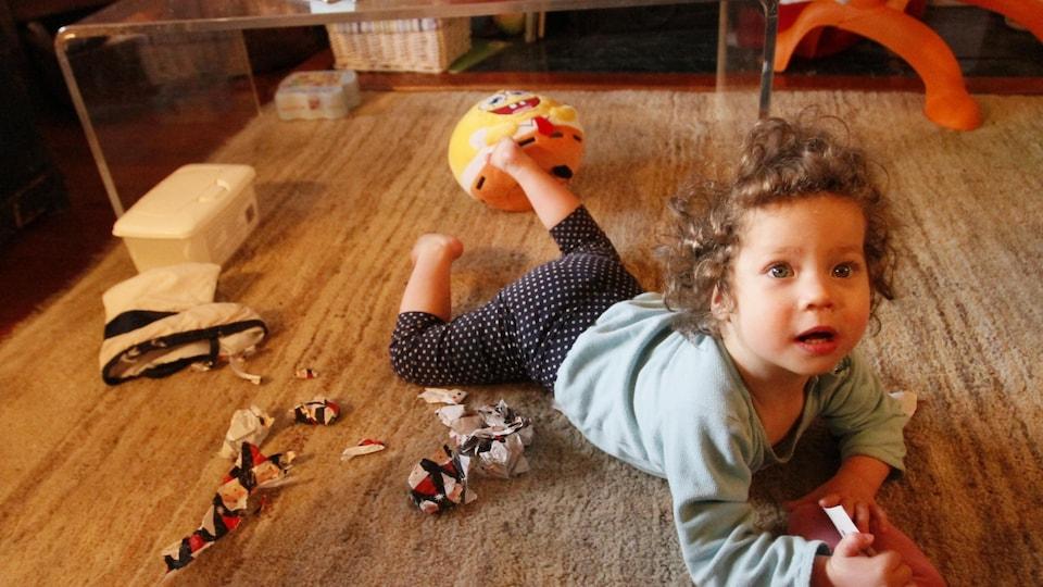 Une petite fille sur un tapis de jeu.
