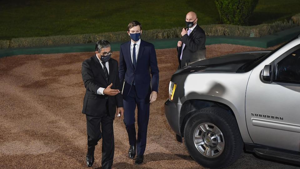 Trois hommes dans un jardin devant une voiture stationnée.