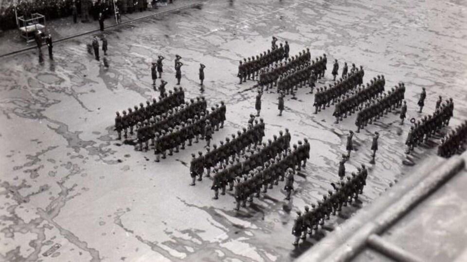 Photo aérienne d'une parade militaire où les aviatrices sont postées en rangées.