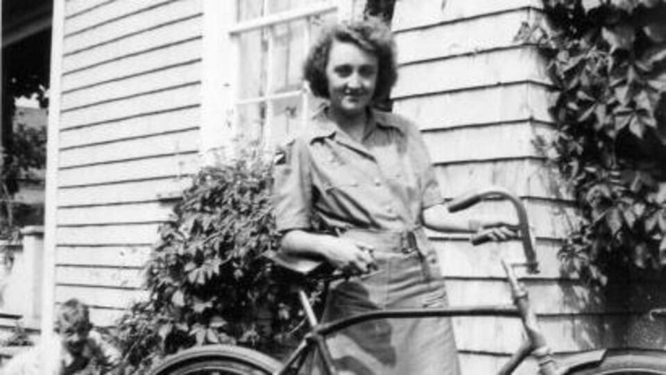 Martha Arsenault est photographiée avec une bicyclette devant une maison de Bonaventure (photo en noir et blanc).