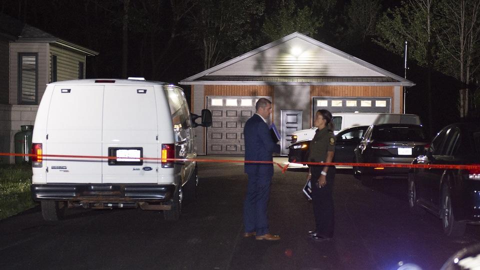 Deux policiers discutent devant le garage d'une maison.