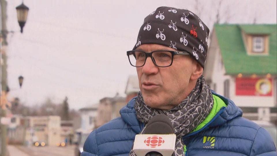 Martin Deschênes en entrevue sur le trottoir d'une rue passante de Montebello.