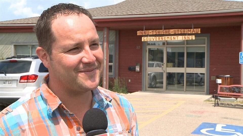 Martin Dufour porte une chemise à carreaux. Il sourit à la caméra.