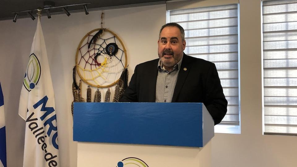 Martin Ferron parle derrière un lutrin avec le logo de la MRC.