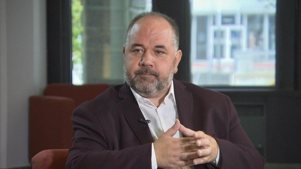 Martin Francoeur assis dans un fauteuil durant une entrevue.