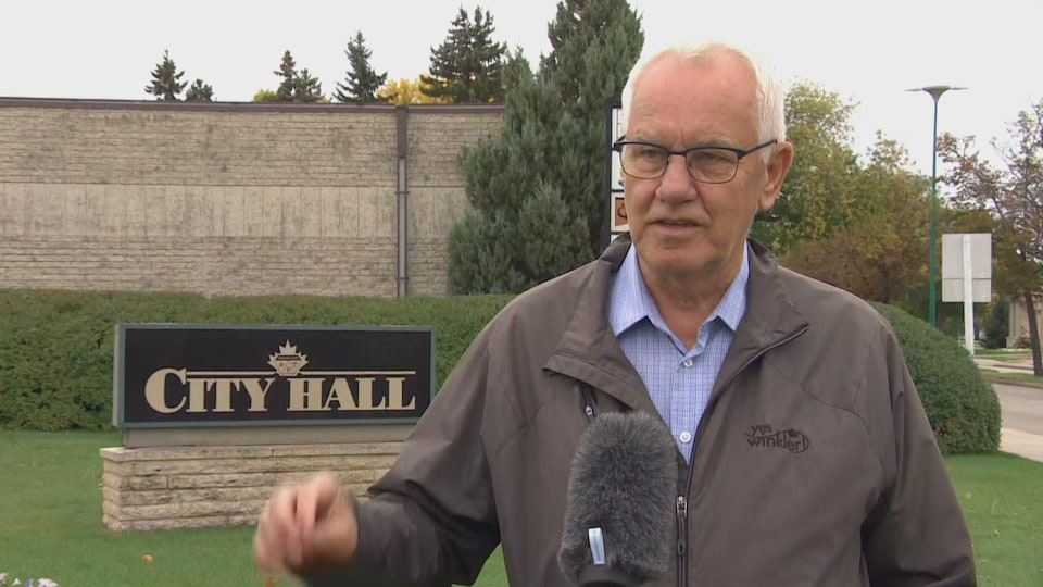 Martin Harder est vêtu d'une chemise bleue et d'un manteau brun. Il donne une entrevue devant l'enseigne de l'hôtel de ville de Winkler.
