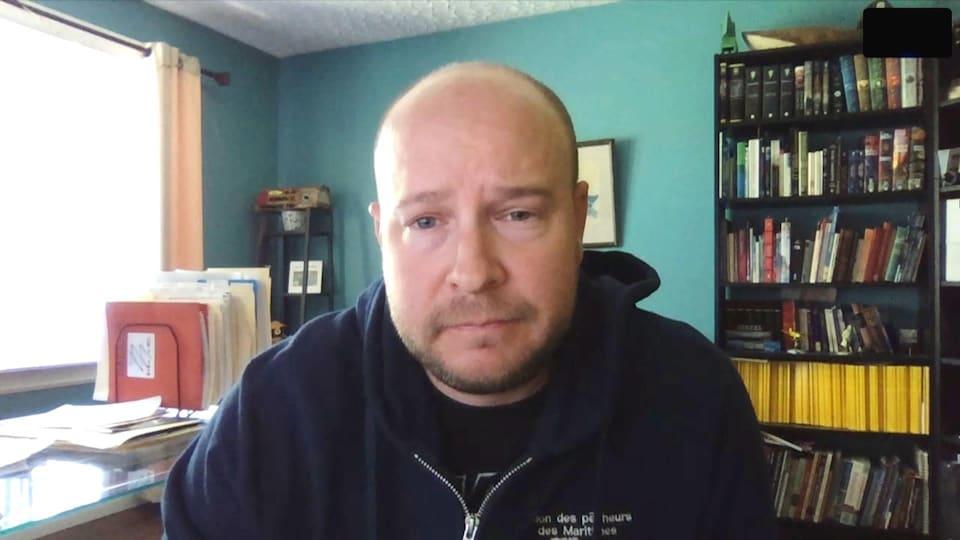 Martin Mallet en entrevue par webcam. Il est assis dans un bureau.