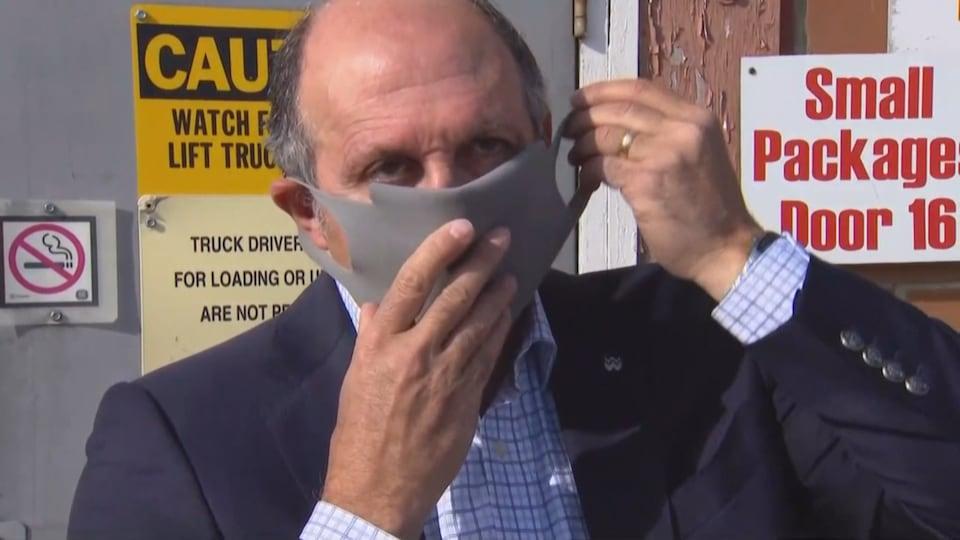 Un homme enfile un masque gris.
