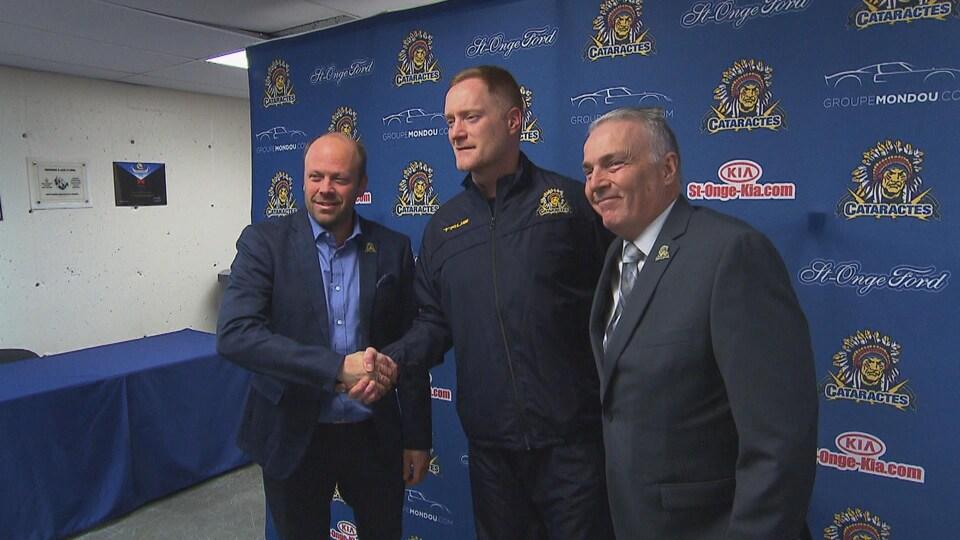 Trois hommes souriant devant des caméras.