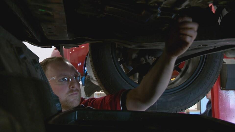 Un homme inspecte le dessous d'une voiture.