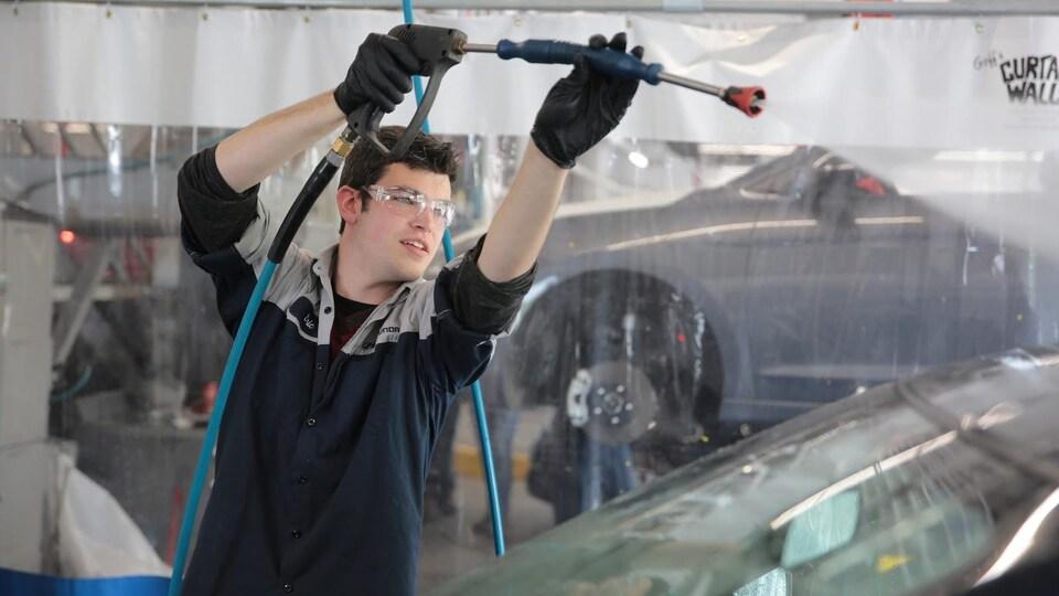 Un homme arrose le pare-brise d'une voiture dans un atelier de mécanique