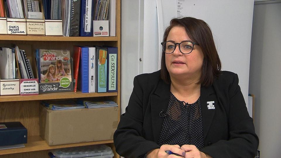Martine Girard est assise dans son bureau, elle regarde la caméra.