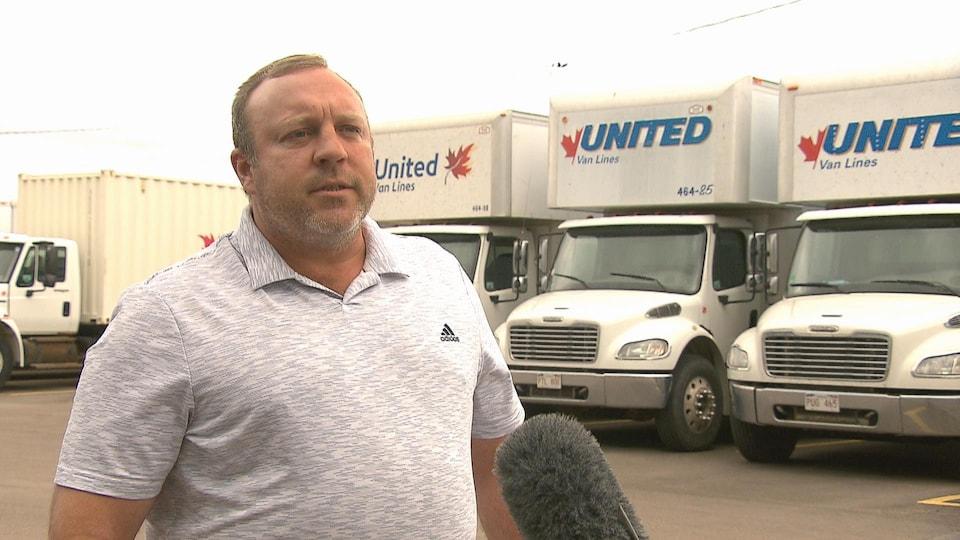 Marty Wry donnant une entrevue à l'extérieur devant des camions de déménagement.