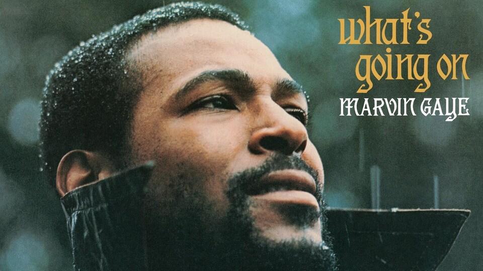 Marvin Gaye, vêtu d'un imperméable noir, se tient sous la pluie.