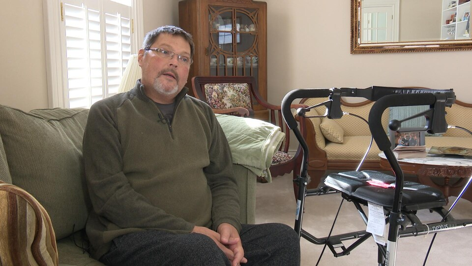 Marvin Switzer est assis sur un divan dans son salon.