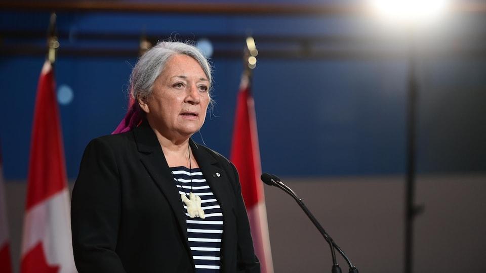 Mary Simon face à un micro, devant deux drapeaux canadiens.