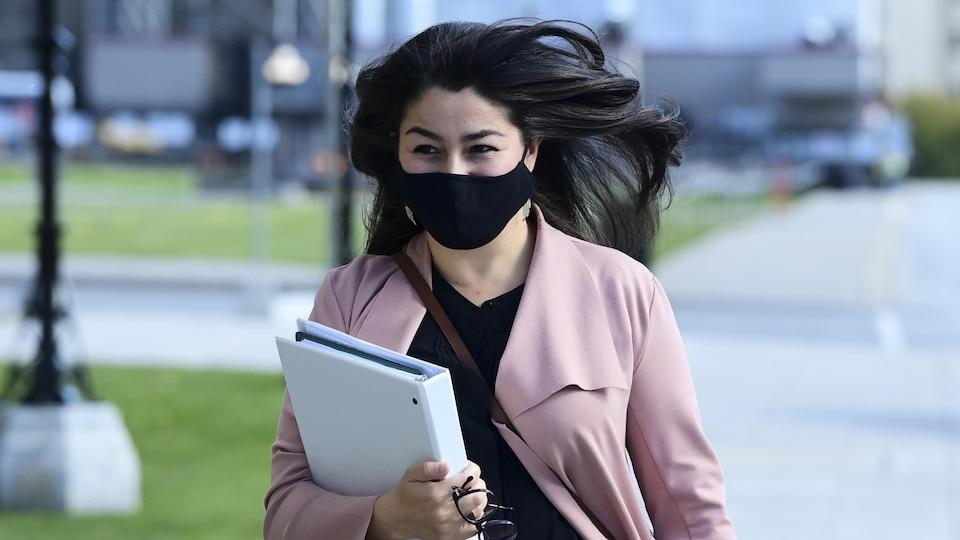 La ministre libérale Maryam Monsef porte un classeur.