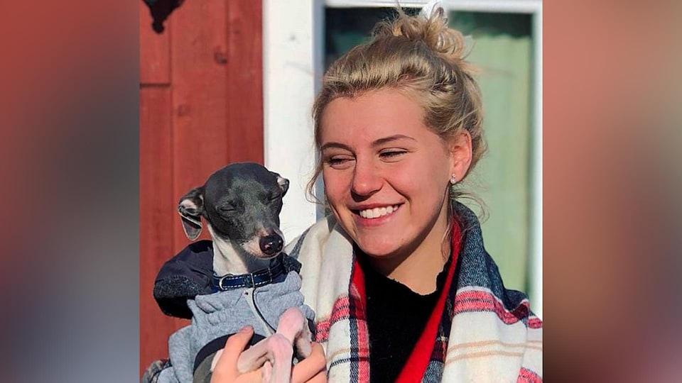 Marylène Levesque souriante, tient un petit chien dans ses bras.