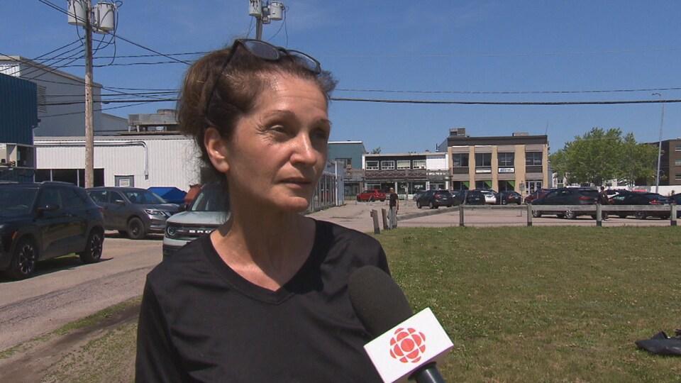 Maryse Morneau parle au micro de Radio-Canada et elle se trouve sur la future place Mingan, qui est actuellement un terrain vague vert.