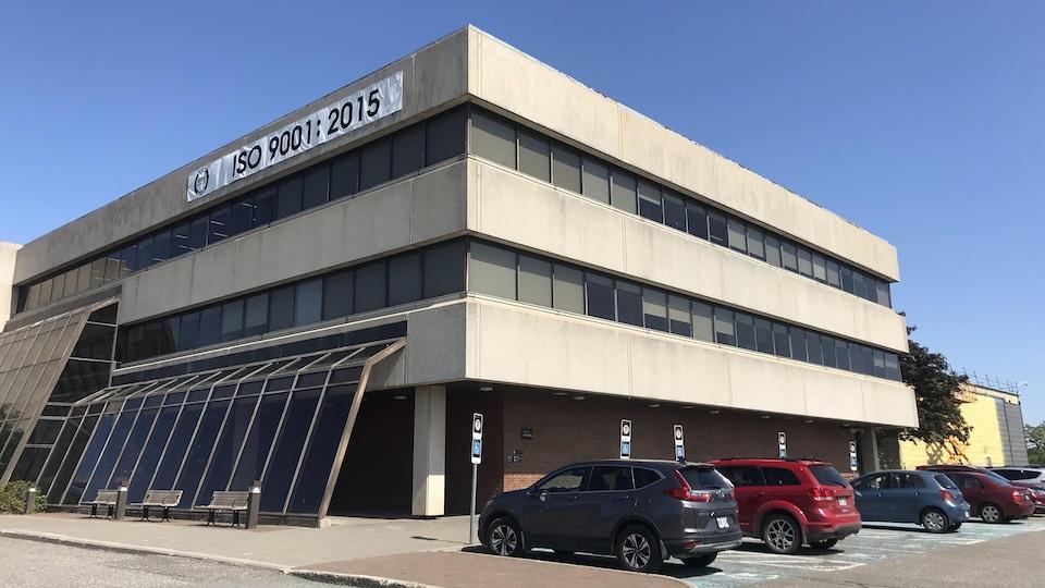 Des véhicules sont stationnés devant un bâtiment. Il s'agit de l'édifice de Travaux publics et Services gouvernementaux du Canada à Matane.