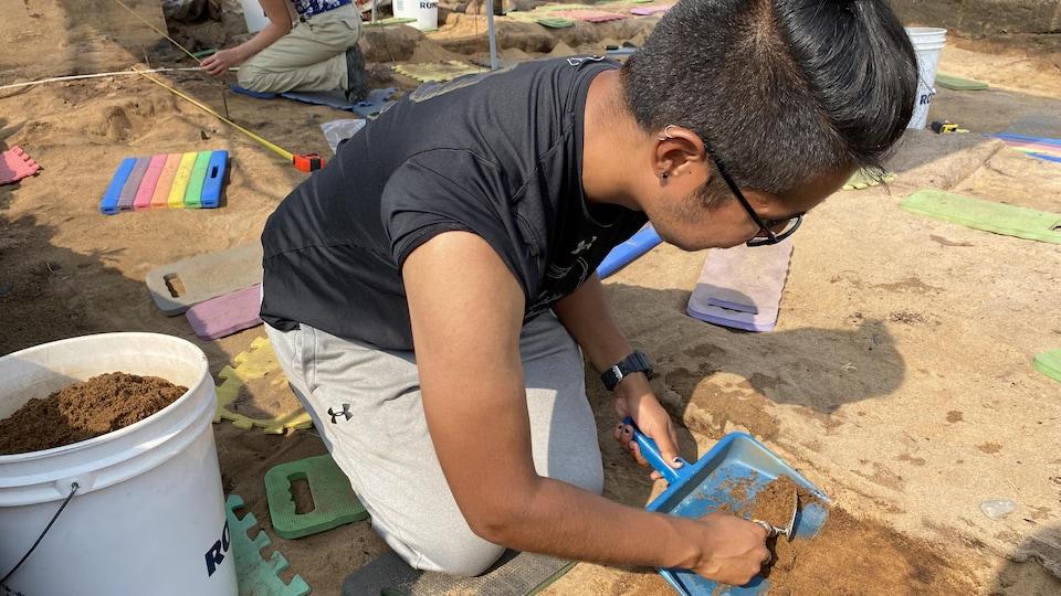 Un jeune homme gratte le sol en quête d'artefacts.