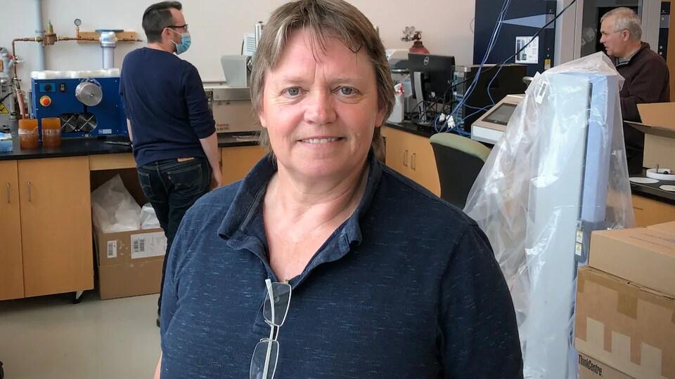 Beth Mason dans son laboratoire. Deux autres chercheurs travaillent en arrière-plan.