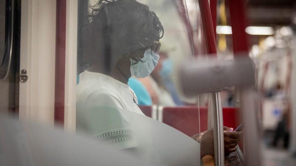 Une femme portant le masque dans un autobus regarde son cellulaire.