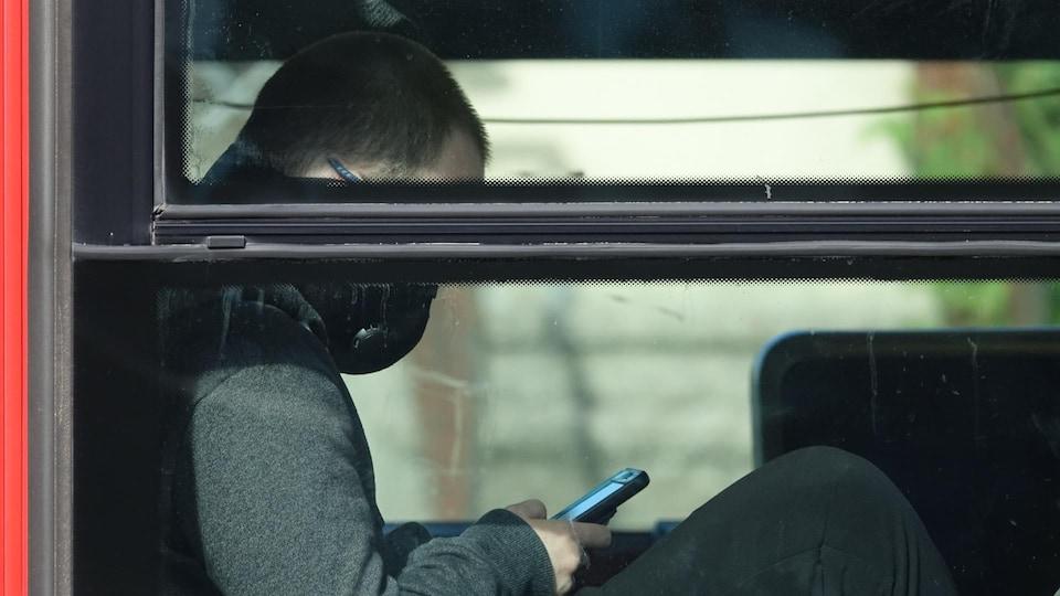 Un homme assis dans un autobus porte un masque.