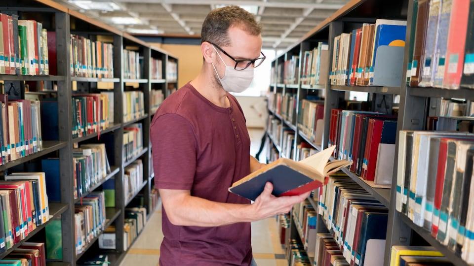 Un homme portant un masque feuillette un livre dans une bibliothèque.