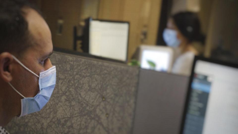 Deux travailleurs portent le masque devant leur écran d'ordinateur.
