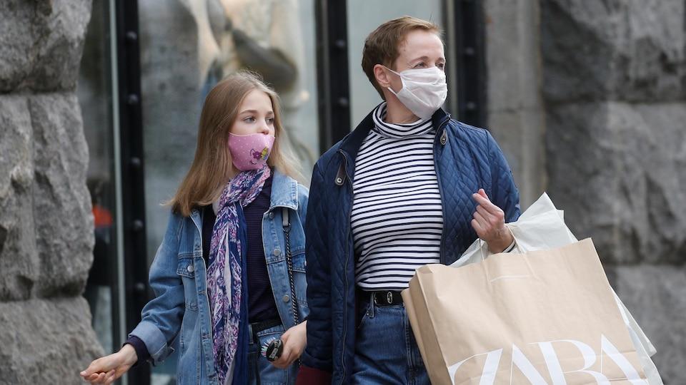 Une femme adulte et une adolescente marchent dans la rue à Kiev le 22 octobre 2020. Ils portent des masques et transportent des sacs d'une boutique de vêtements.