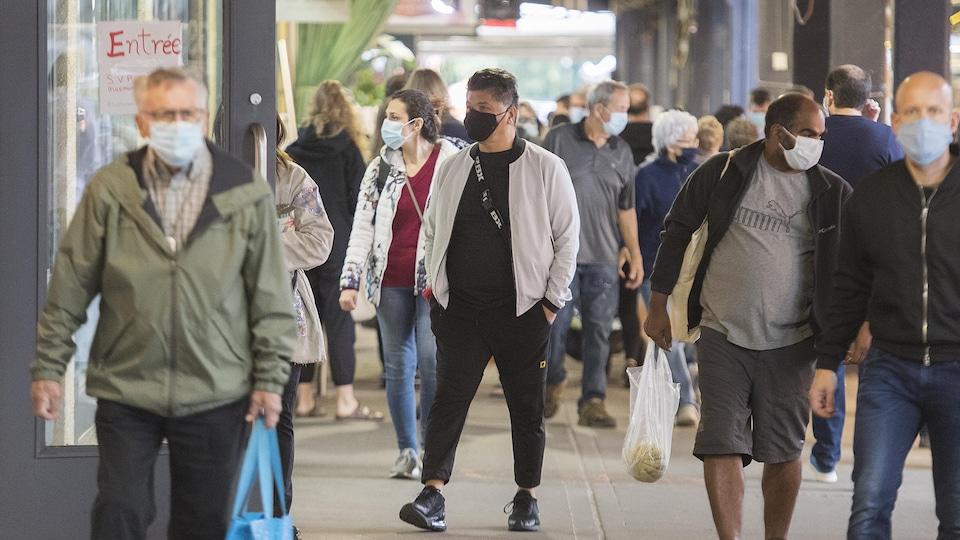 Des gens qui portent un masque se promènent dans un marché extérieur.