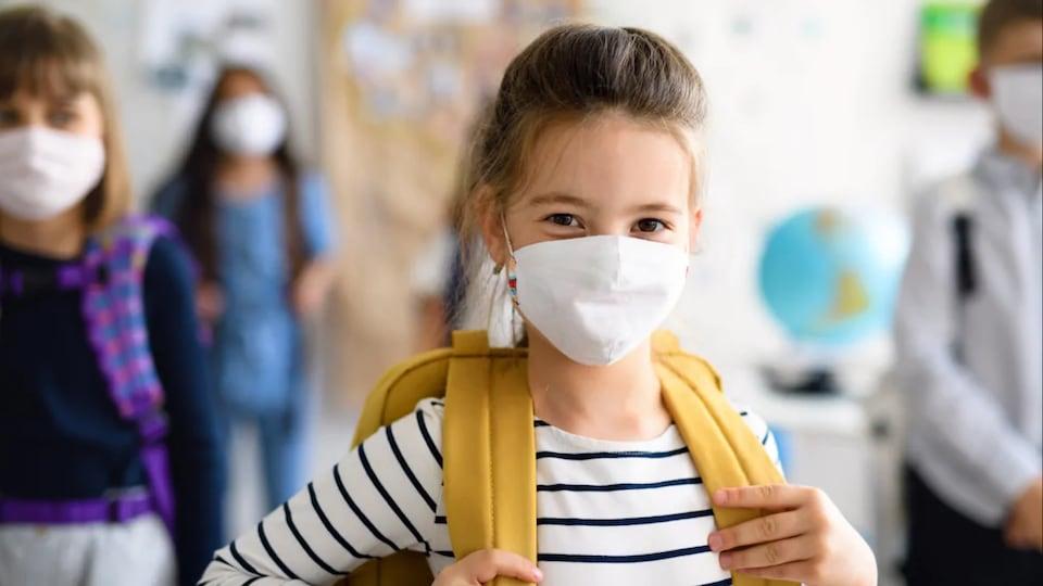 Une jeune élève portant un masque à l'école.