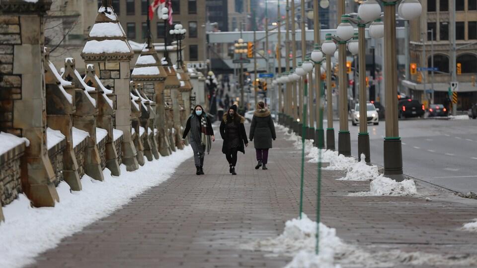 Des gens marchent sur le trottoir du centre-ville d'Ottawa.