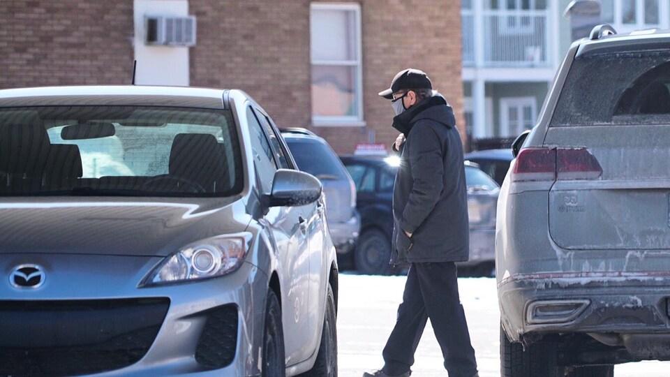 Un passant marche à l'extérieur et porte un masque.